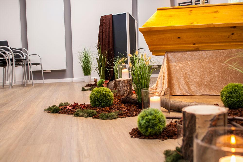 Rindenmulch, Pflanzen und Kerzen als Dekoration für eine Trauerfeier mit Waldbestattung in Hannover