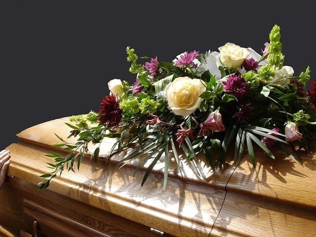 Sarg bei der Trauerfeier mit Blumengesteck