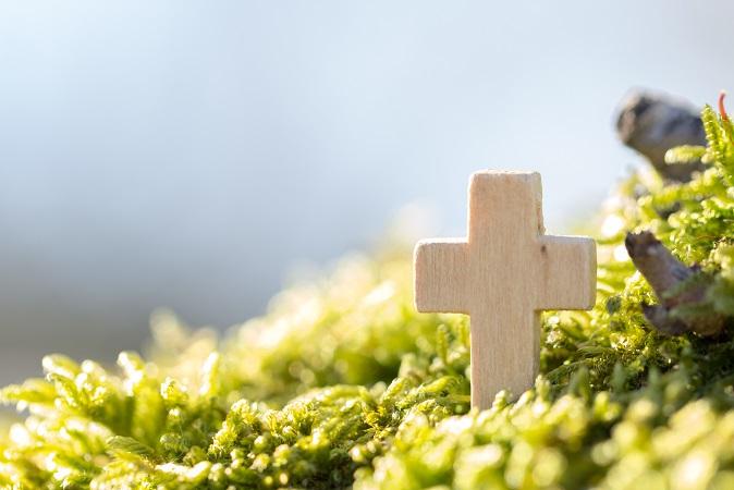 Holzkreuz im Grünen vor blauem Himmel