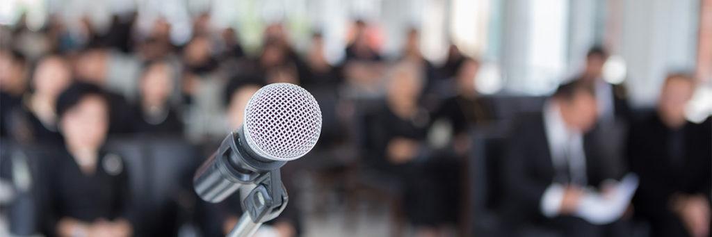 Mikrofon steht von Trauergemeinde als Symbol für Trauerrede