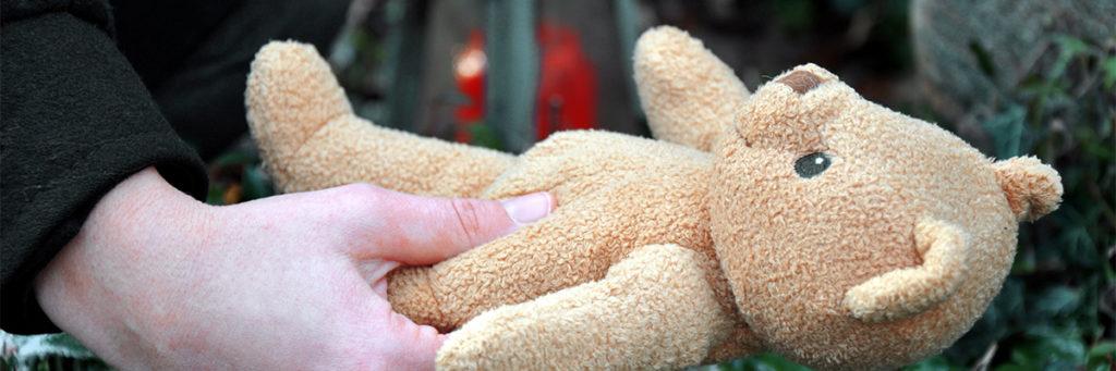 Teddybaer wird auf Kindergrab gelegt als Symbol für Kinderbestattung