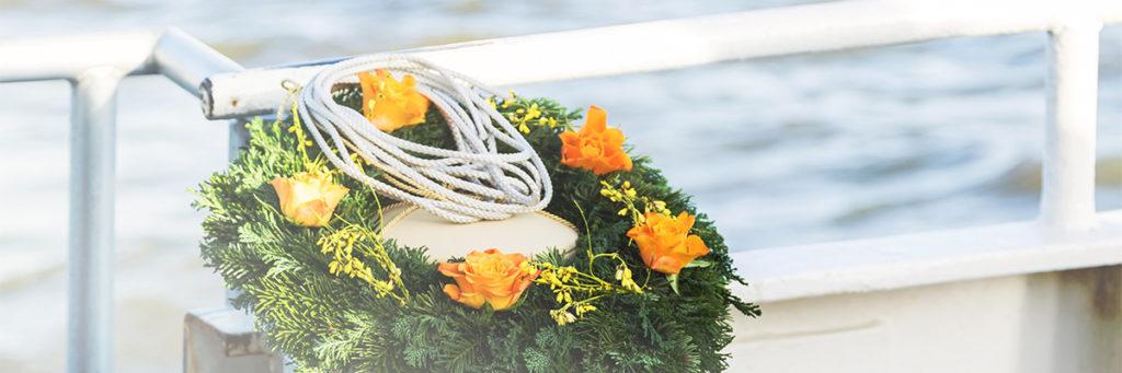 Blumenkranz und Urne auf einem Boot als Symbol für Bestattungsarten ohne Kirche